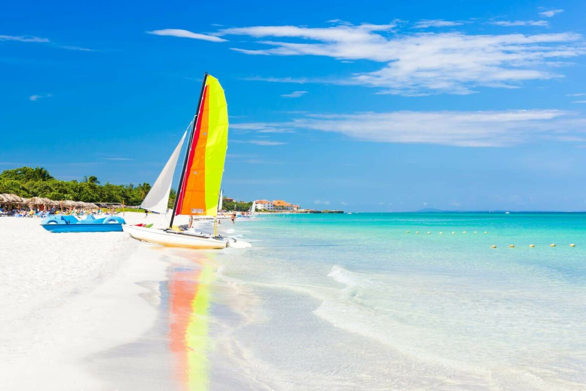 A sunny day ina white sand beach of Varadero in Cuba with a rainbow coloured sailboat