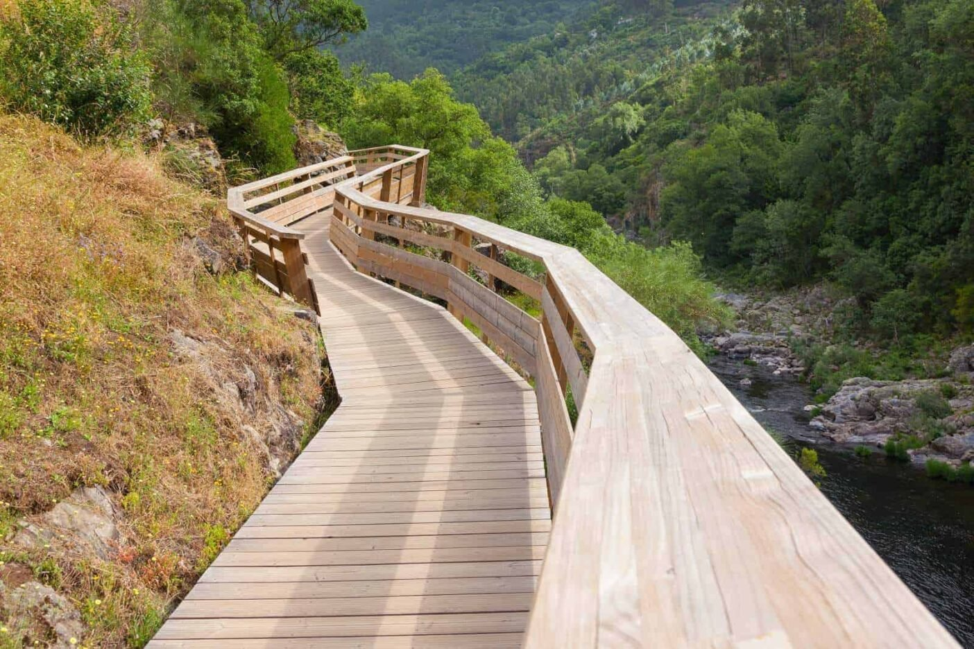 Wooden walkways clinging to the mountain sides along the Aveiro river with a view of a green valley and forests