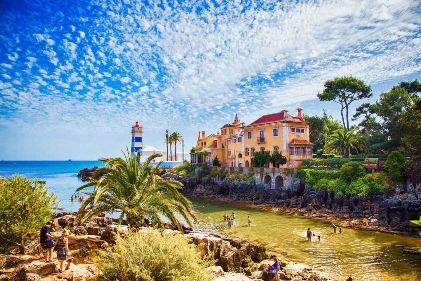 A blue and white lighthouse at the entrance to a blue water bay framed by palm trees Santa Marta Lighthouse to the south of the centre of Cascais