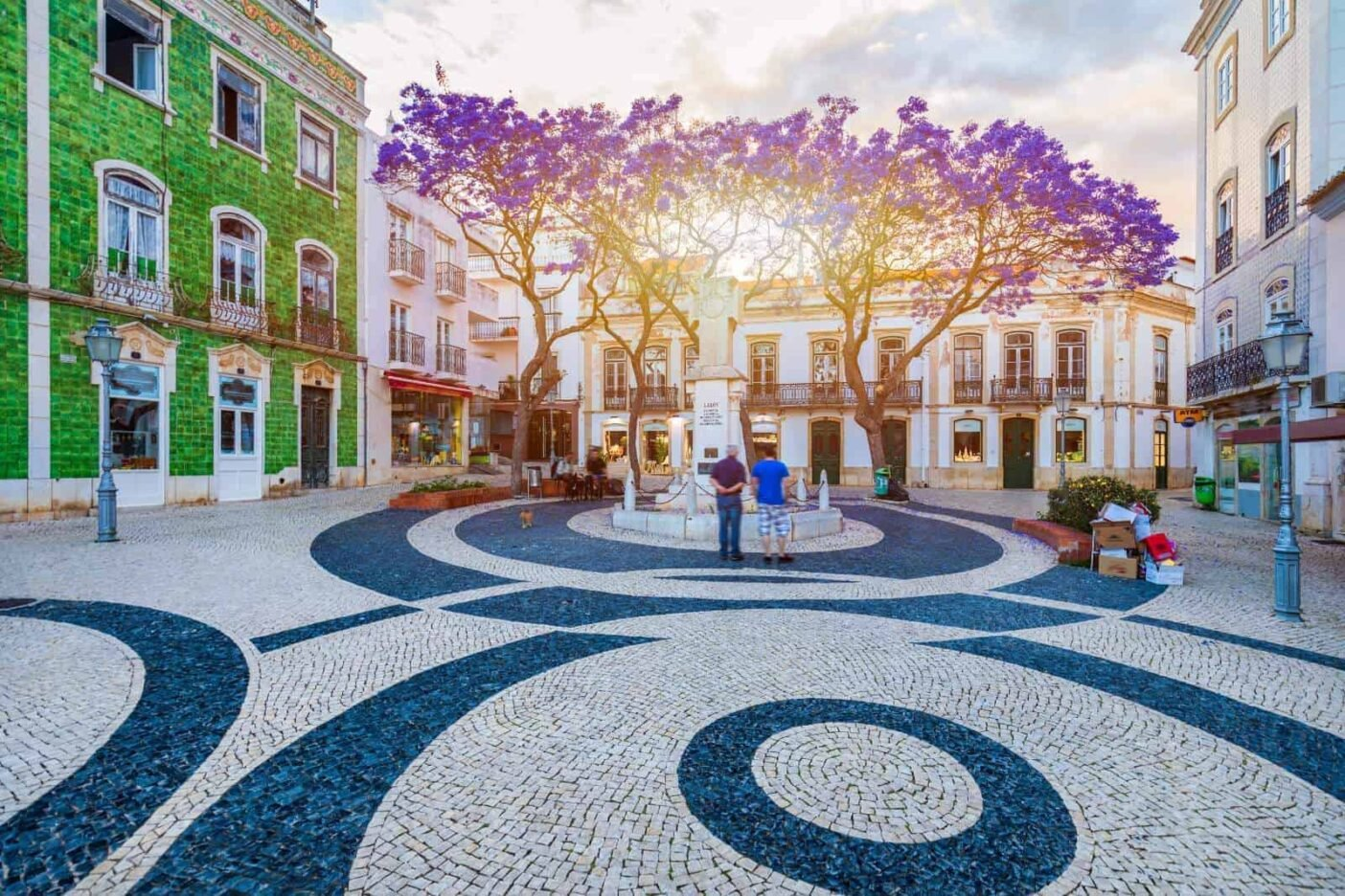 A spacious town square in Lagos, Portugal with white and blue mosaic and a tree full of purple blossom in the centre