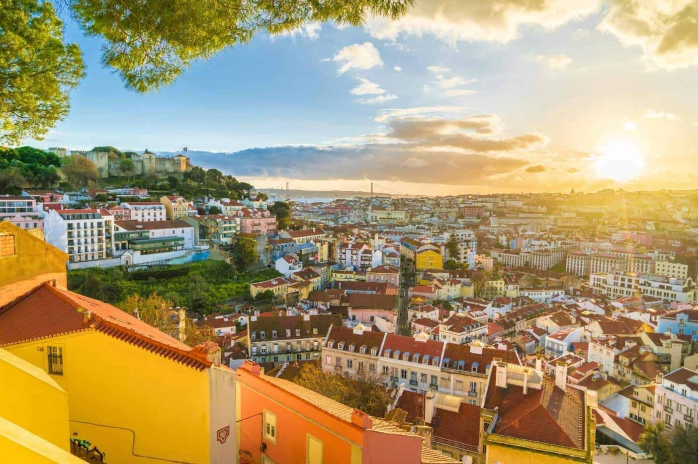 Down the hill view of Lisbon: colourful houses and brown roofs mingled with parks at sunset