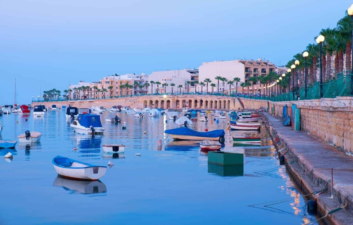 Best places to live in malta - stunning Marsaskala waterfront with traditional Maltese fishing boats sheltered for the night, Malta