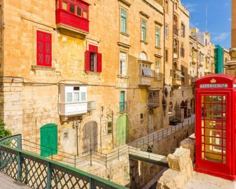 Valletta, Malta - street view with traditional British red phone box and red Maltese balconies