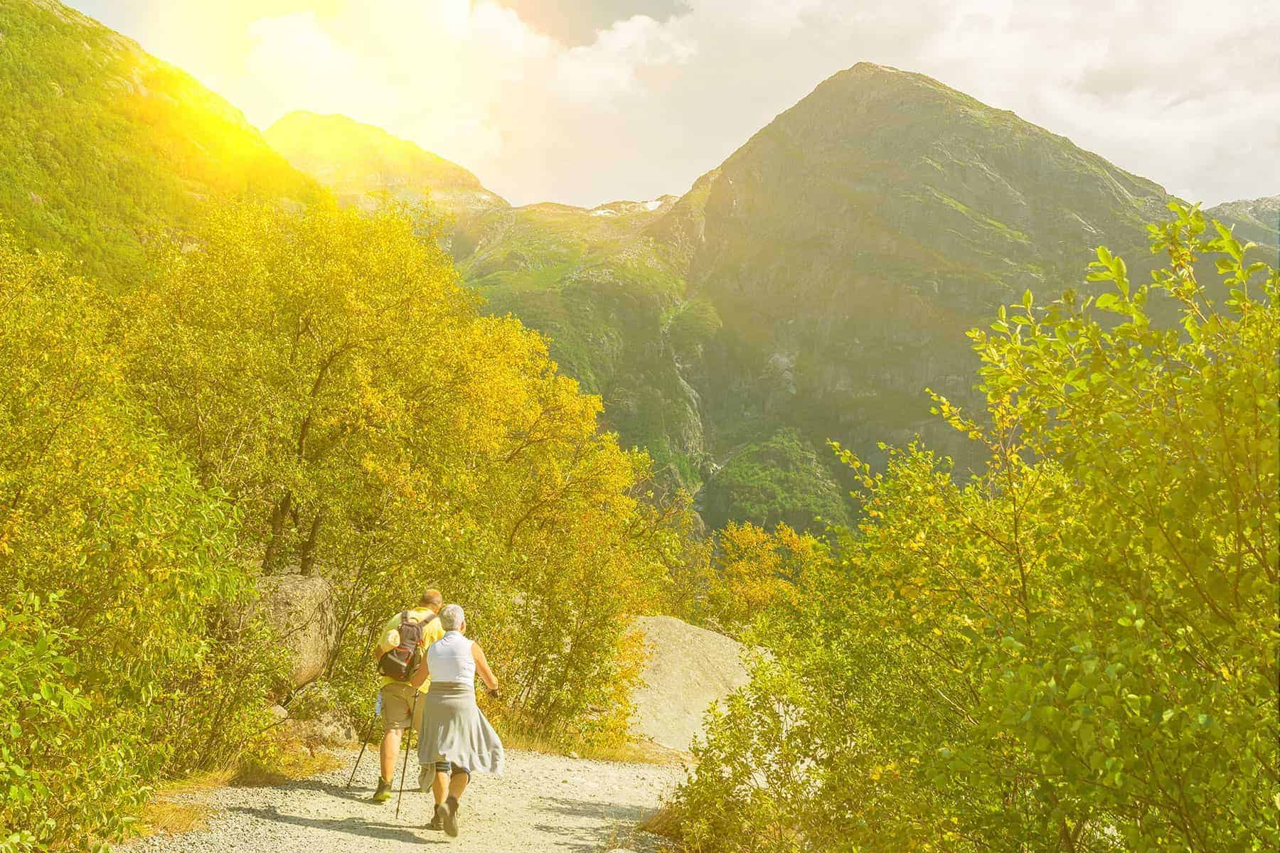 Keeping healthy in retirement - a retired couple walking in the mountains on a bright sunny days