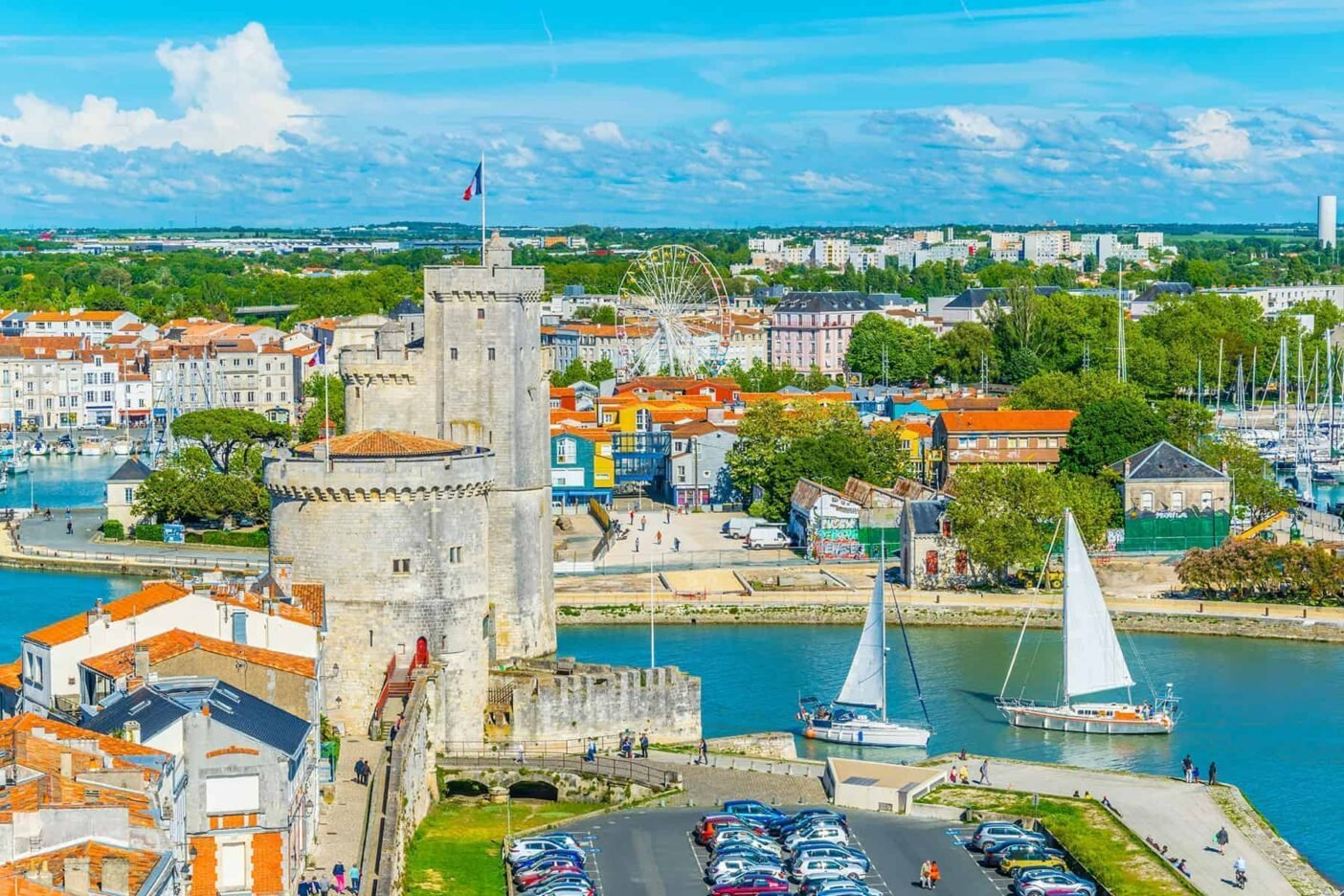 La Rochelle: a stone rower and a beautiful harbour with sailing boats on a sunny day