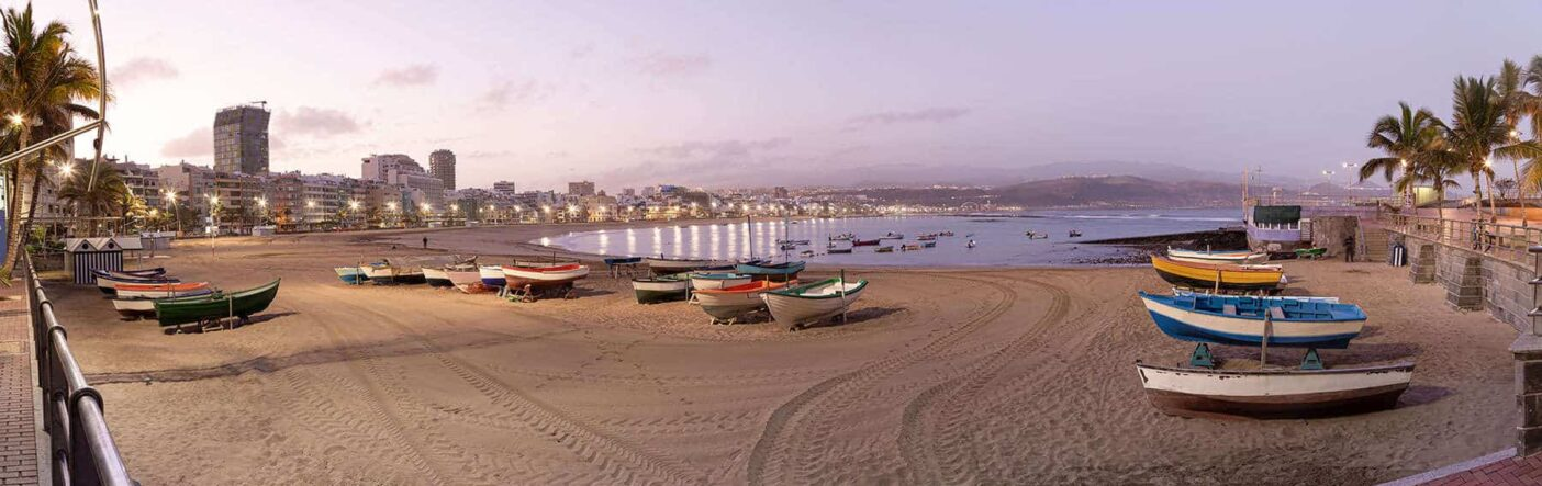 A sandy beach with boats surrounding a quiet bay in Las Palmas, Spain